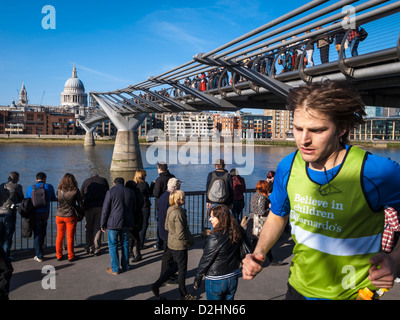 a young man running under millenium bridge in a sunny day - Stock Photo
