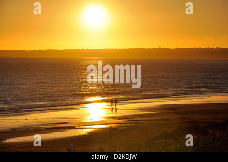 Couple walking in on beach at sunset in Gale, Faro District, Algarve Region, Portugal - Stock Photo