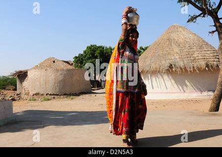 Mir tribal woman carrying water in steel pot, Gujarat, India, Asia - Stock Photo