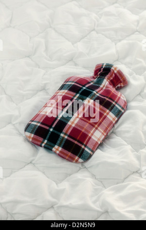 a vintage hot-water bottle on a duvet - Stockfoto