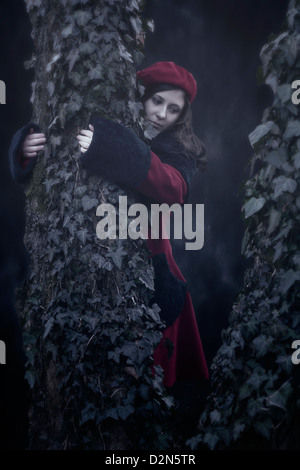 a woman in a red coat is hugging an old tree with ivy - Stock Photo