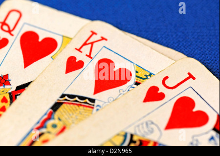 Close-up of three playing cards - Jack, Queen and Jack of Hearts on a blue background - Stock Photo