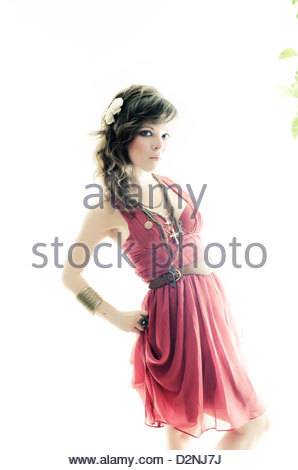 Portrait of a young woman in a pink dress looking at camera standing against a white background. - Stock Photo
