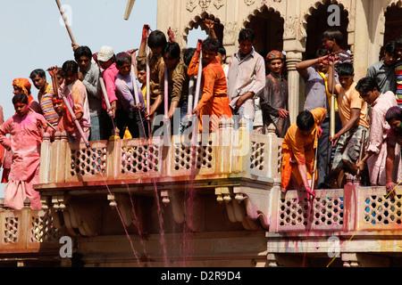 Young men celebrating Holi festival by splashing colored fluids on temple visitors, Nandgaon, Uttar Pradesh, India, - Stock Photo