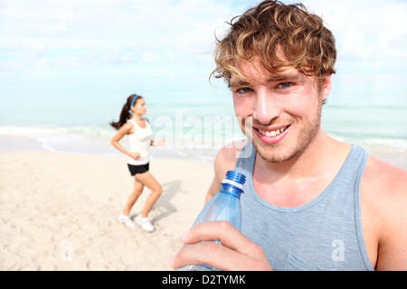 Portrait of fit young man drinking water with woman jogging in background on beach - Stock Photo