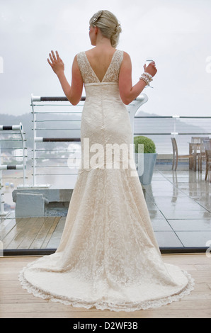 A pretty young blond bride looking out of a window as she waits for her wedding ceremony. - Stockfoto