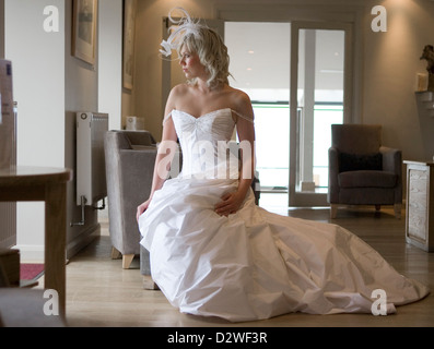 A pretty young blond bride wearing a wedding dress and looking pensively out of a window. - Stockfoto
