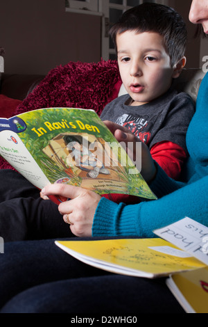 Mother helps  5 years old child to read a book - Stock Photo