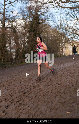 Cross Country Championships senior and inter youth girls extremely muddy conditions on a slope striding down to - Stockfoto