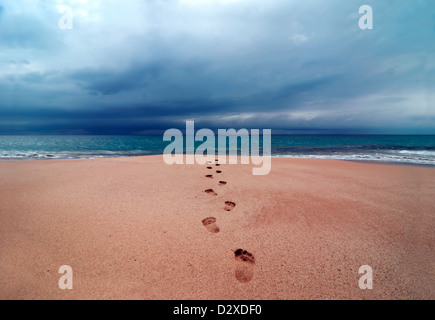 Big storm with clouds over footprints in soft sand leading into the ocean, Papohaku Beach, Molokai, Hawaii, USA, - Stock Photo