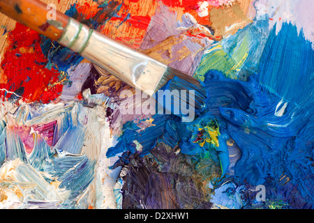 Artists oil paint palette and brush multi coloured closeup. Shallow depth of field. - Stock Photo