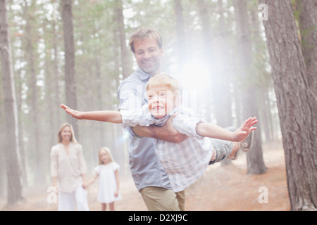 Father flying son in sunny woods - Stock Photo