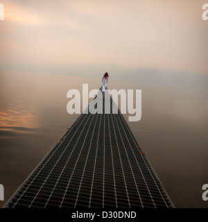 a woman in a white dress is walking on a long bridge over a lake - Stock Photo