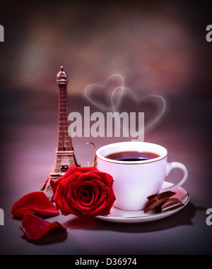 Picture of white cup with coffee and chocolate decorated with red rose on the table in Paris, romantic honeymoon - Stock Photo