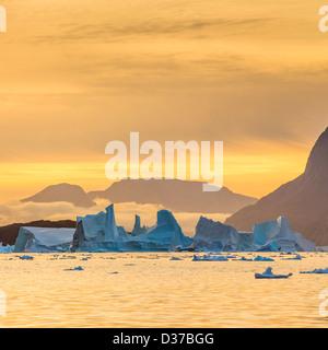 Sunset over drifting Icebergs, Scoresbysund, Greenland - Stock Photo