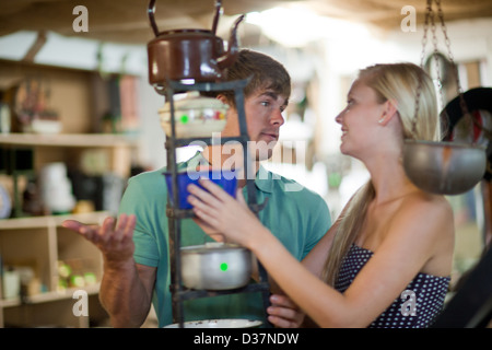 Couple shopping together in thrift store - Stock Photo