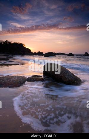 Waves washing over rocks on beach - Stock Photo