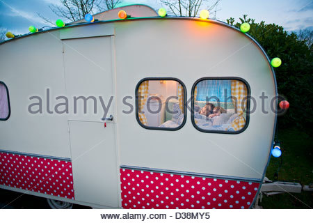 Children relaxing in bed in camper - Stockfoto