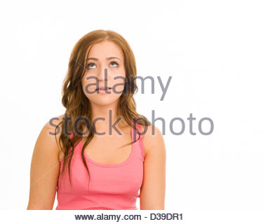 Young woman in a pink tank top on a white background. She is looking up with a questioning look on her face. - Stock Photo