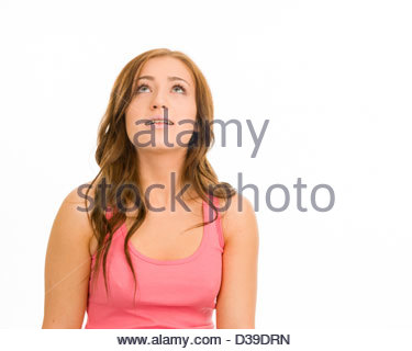 Young woman in a pink tank top on a white background. She is looking up smiling. - Stock Photo