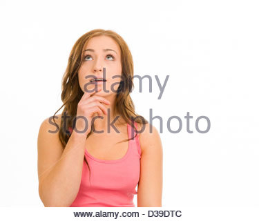 Young woman in a pink tank top on a white background. She is looking up with her finger on her chin as if thinking. - Stock Photo