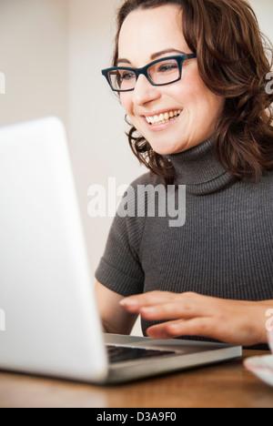 Businesswoman using laptop at desk - Stockfoto