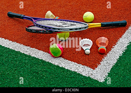 Badminton colored shuttlecocks with tennis balls and rackets, placed in the corner of a synthetic field. - Stock Photo