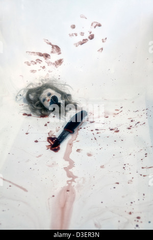 broken head of a doll in a bloody bath tub with a knife - Stock Photo