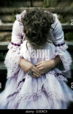 a woman in a wedding dress is sitting on old stone steps - Stock Photo