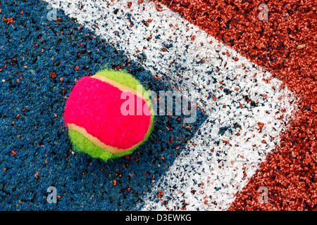 Tennis colored ball placed in the corner of a synthetic field. - Stock Photo