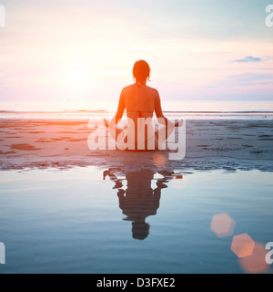 Woman practicing yoga on the beach at sunset, with reflection in water. - Stock Photo