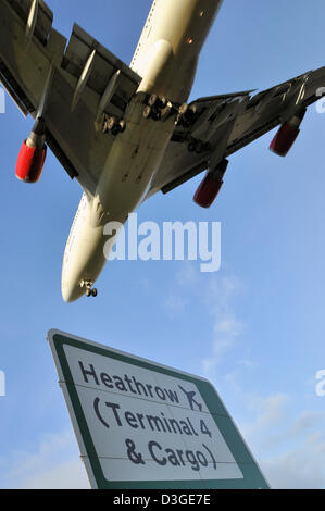A Boeing 747 lands at London Heathrow Airport, as illustrated by the road sign. - Stock Photo