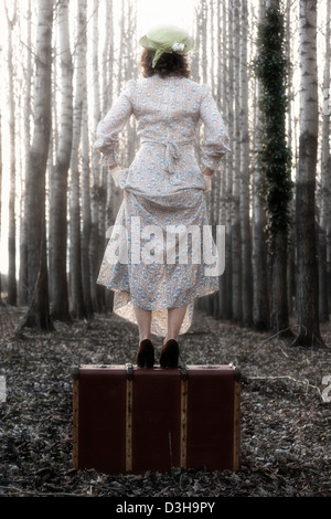 a woman in a floral vintage dress is standing on an old suitcase - Stock Photo
