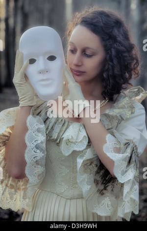 a woman in a period dress is holding a white mask - Stock Photo