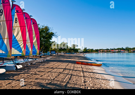 Line of catamaran sailboats with colorful sails early morning on Negril beach and kayak at the water - Stock Photo