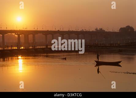 Boat being poled past the Grand Trunk Road bridge at sunset, Maha Kumbh Mela 2001, Allahabad, Uttar Pradesh, India - Stockfoto