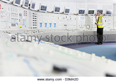 Engineer using walkie-talkie in control room of nuclear power station - Stock Photo