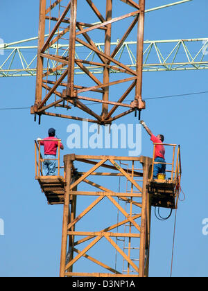 (dpa file) Two workers assemble a crane in Stuttgart, Germany, 29 March 2004. Photo: Juergen Effner - Stock Photo