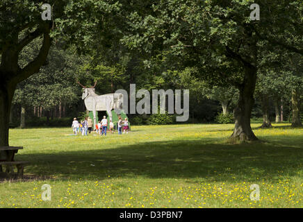 Children playing by wooden figure of a stag in Thetford Forest picnic site - Stock Photo