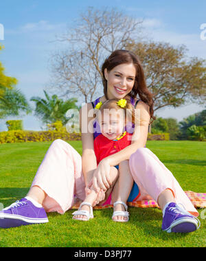 Photo of young mother with cute little daughter sitting down on green grass field in park, beautiful woman with - Stock Photo