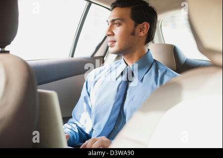 Bengali businessman using a laptop in a car - Stock Photo