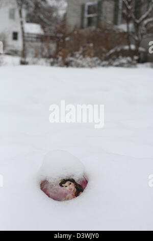 A child's ball buried halfway in the snow. - Stock Photo