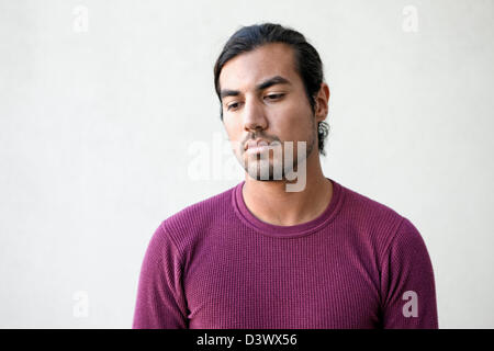 Portrait of sad and depressed young adult mexican-american male in deep thought - Stock Photo