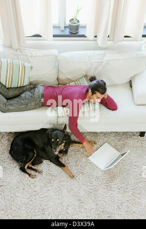 A young casual Hispanic-Latino man entertaining his pet dog by surfing internet using laptop - Stock Photo