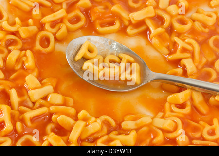 Pasta shaped letters spelling the word PASTA on a spoon within pasta shaped letters in tomato sauce - Stock Photo