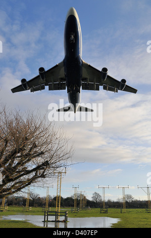British Airways Boeing 747 Jumbo Jet coming in to land at London Heathrow low over the landing lights and flooded - Stock Photo