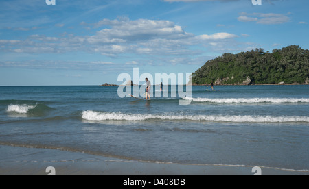 Stand-up paddle-boarding on the beach at Mount Maunganui, Rabbit Island in background. - Stock Photo