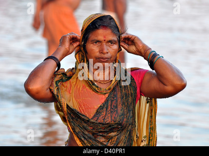 A Hindu devotees pray as stand in the waters of the Sangam or confluence of the Yamuna, Ganges and mythical Saraswati. - Stock Photo