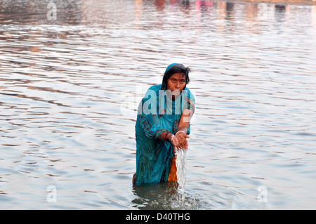 A Hindu devotees pray as stand in the waters of the Sangam or confluence of the Yamuna, Ganges and mythical Saraswati - Stock Photo