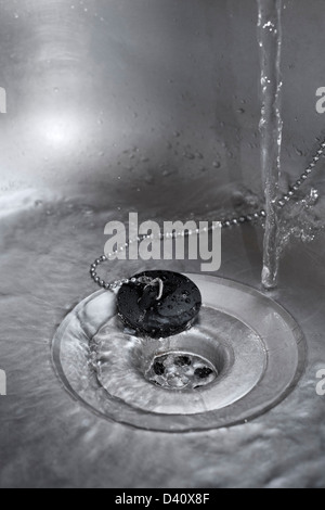 Kitchen sink - Water running down the plughole in a kitchen sink - Stock Photo